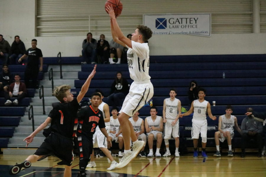 Reece+Posey%2C+a+senior%2C+jumps+high+over+his+defender+to+score+two.