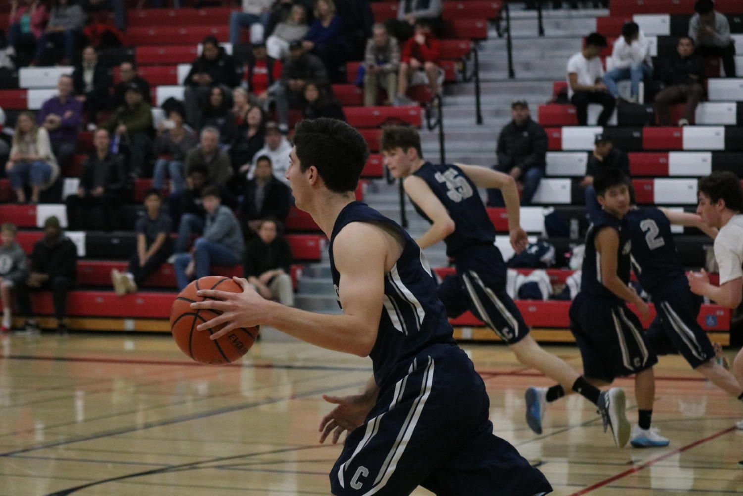 David Bedrosian, a senior and point forward, takes the ball down the court.