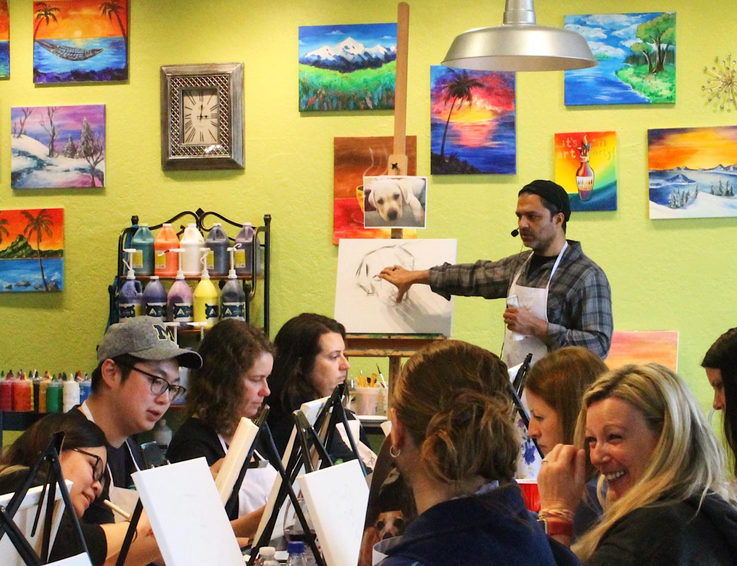 Pet-owners listen to the instructor at Bottle and Bottega to paint portraits of their pets.