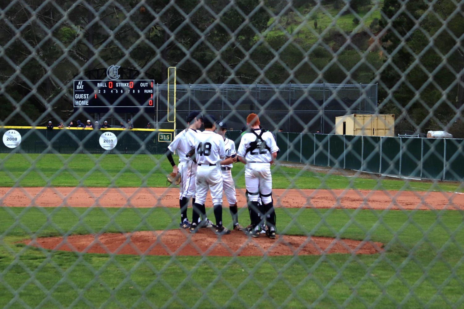 The+Scots+defense+meets+with+the+pitcher+on+the+mound+in+the+1st+inning+of+play.