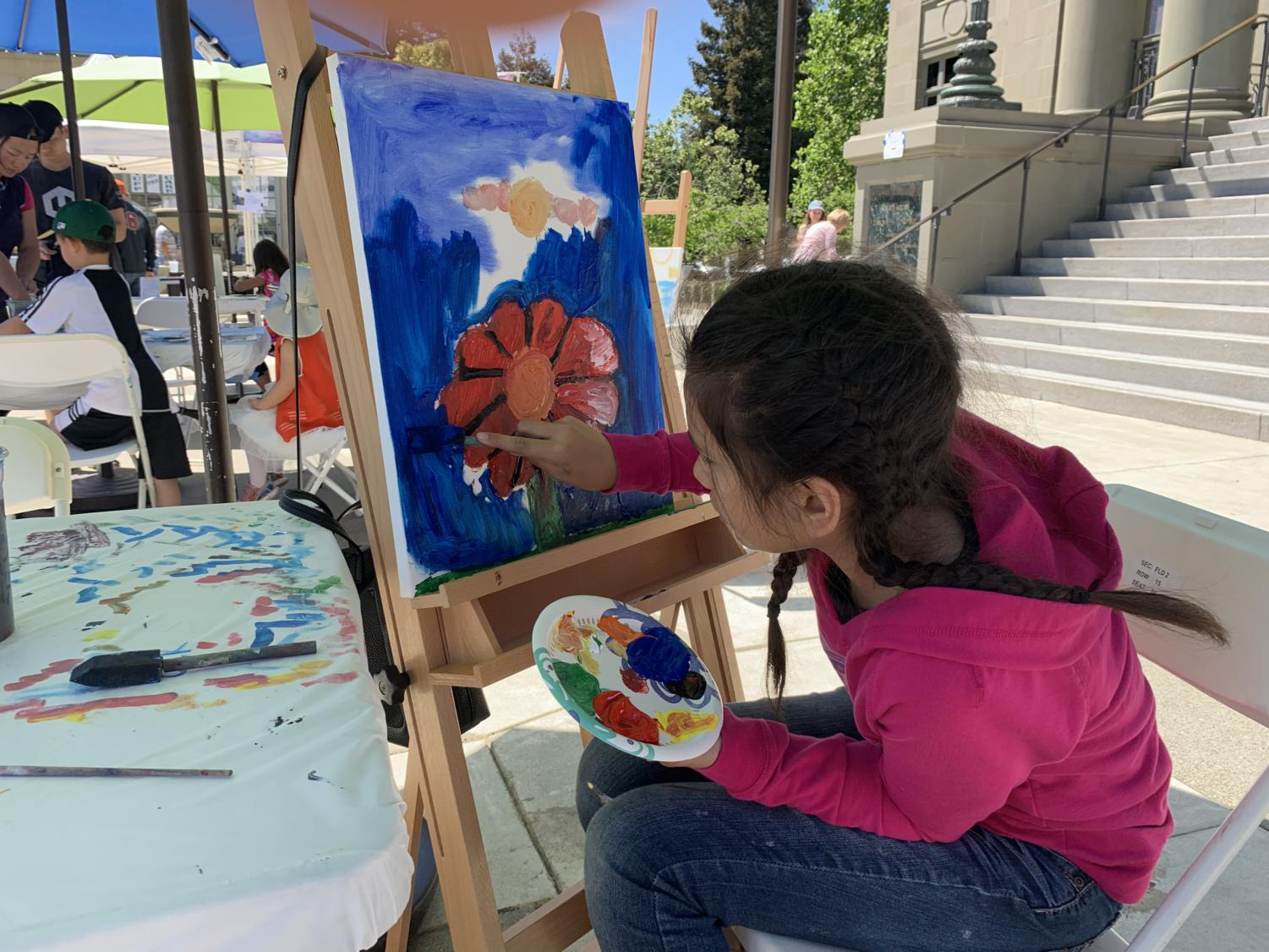A+young+girl+uses+her+finger+to+paint+a+large+red+flower.