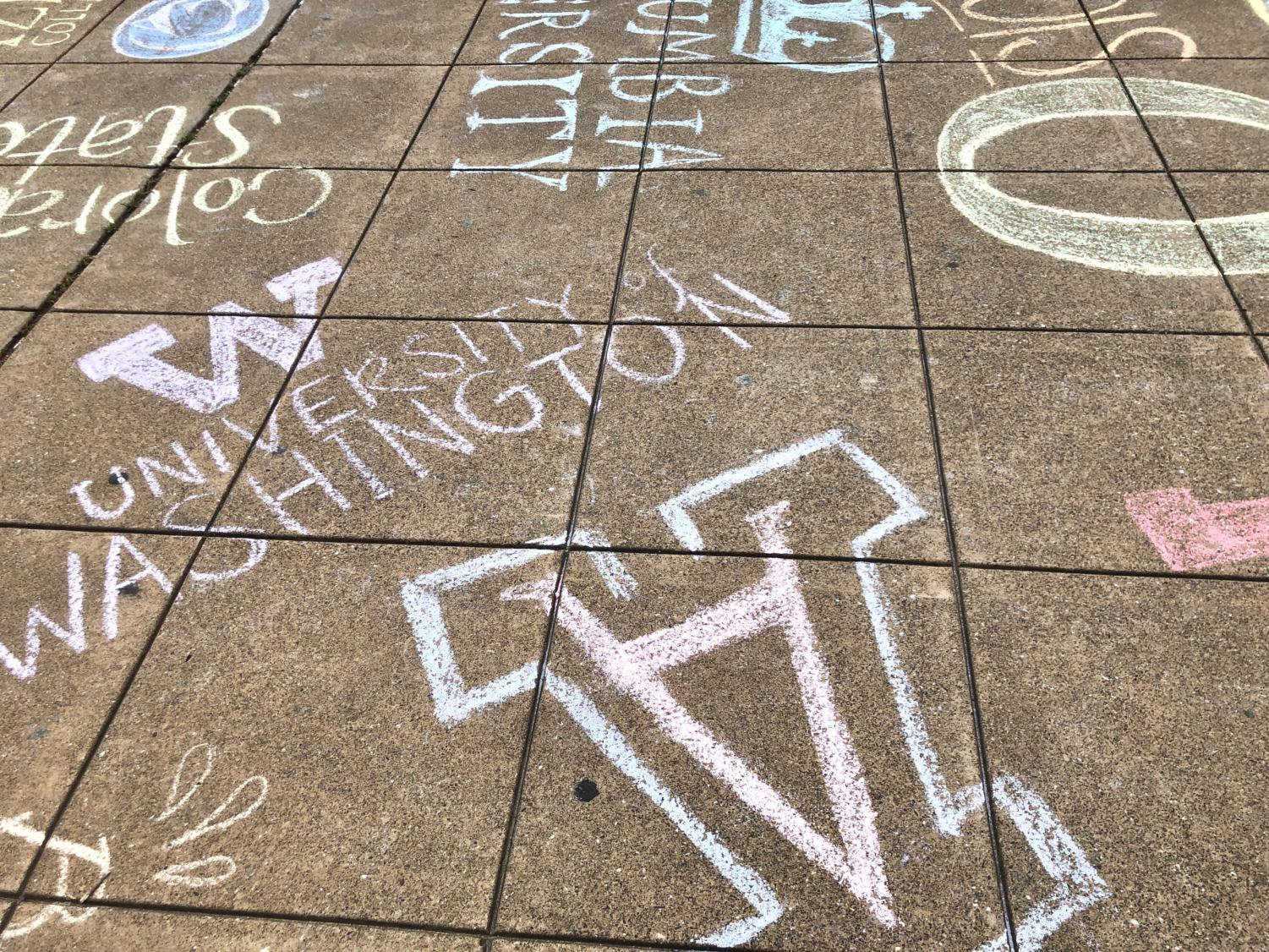 Seniors decorate the quad with chalk logos of their colleges.