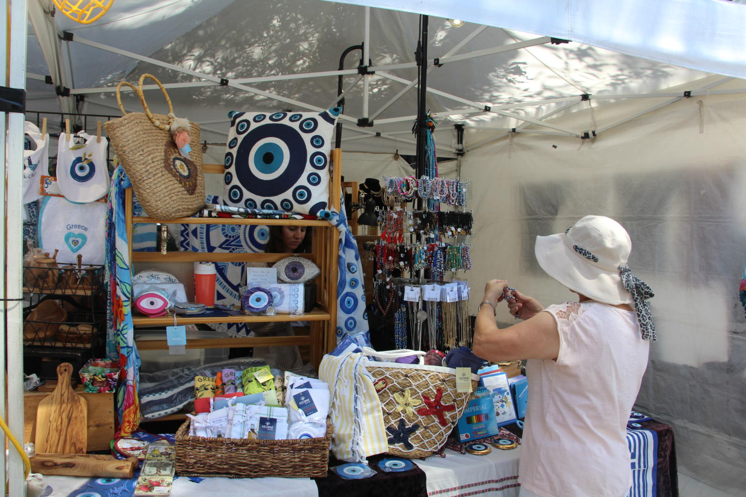 A+visitor+observes+a+bracelet+for+sale+at+the+Beyond+Bella+booth%2C+a+place+that+sells+Greek+cultural+items.