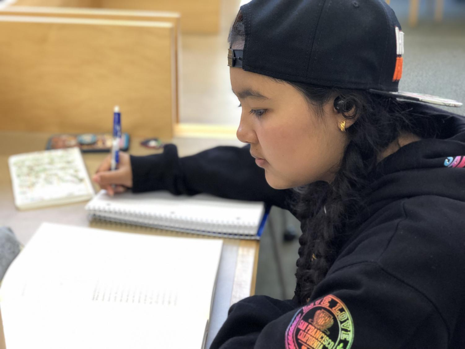 Sophomore Maya Henry prepares for the PSAT using a PSAT prep book from The Princeton Review at the Belmont Library.
