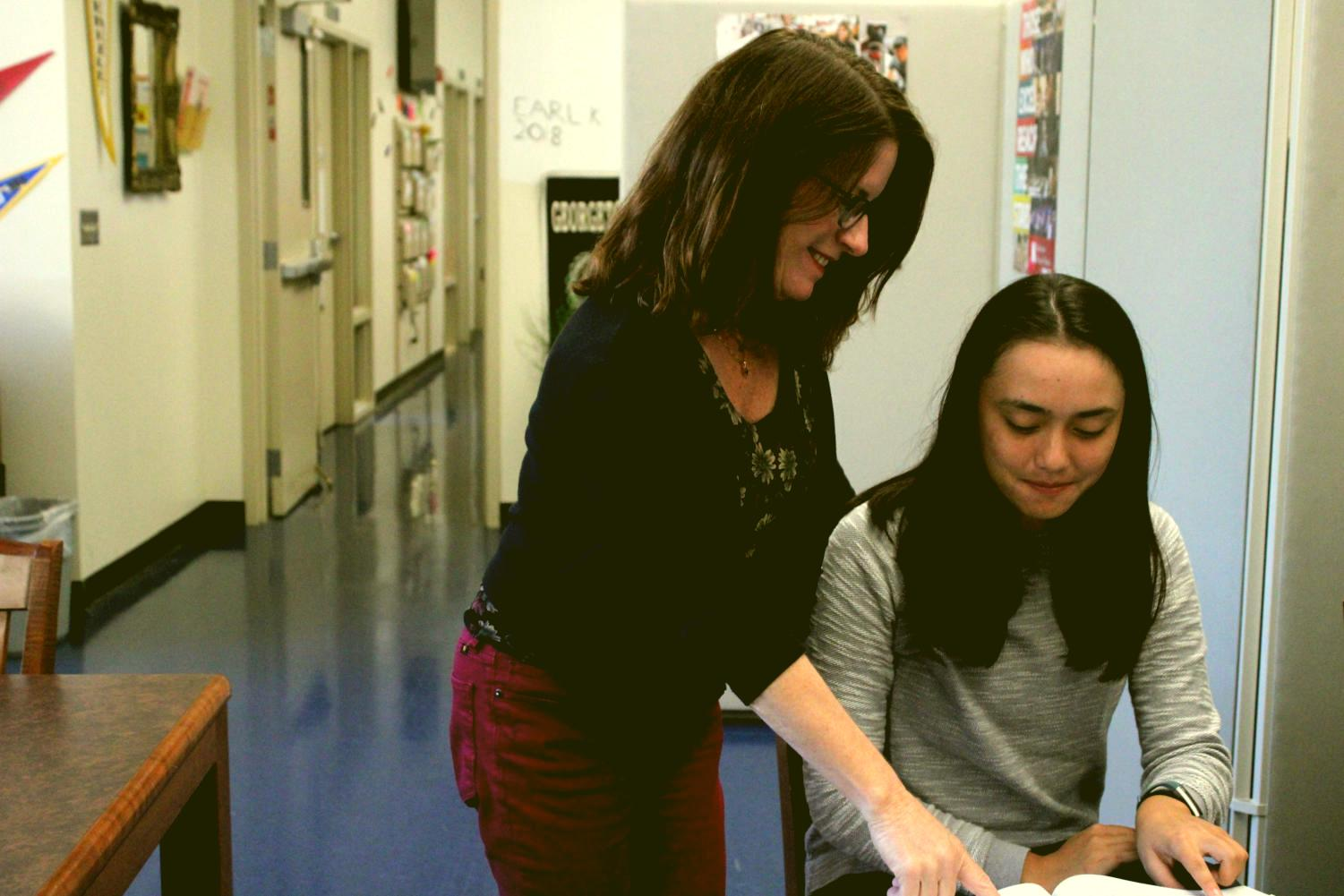 Nina Rasor, a College and Career Center assistant, helps Lilly Gittoes, a senior, with her work.