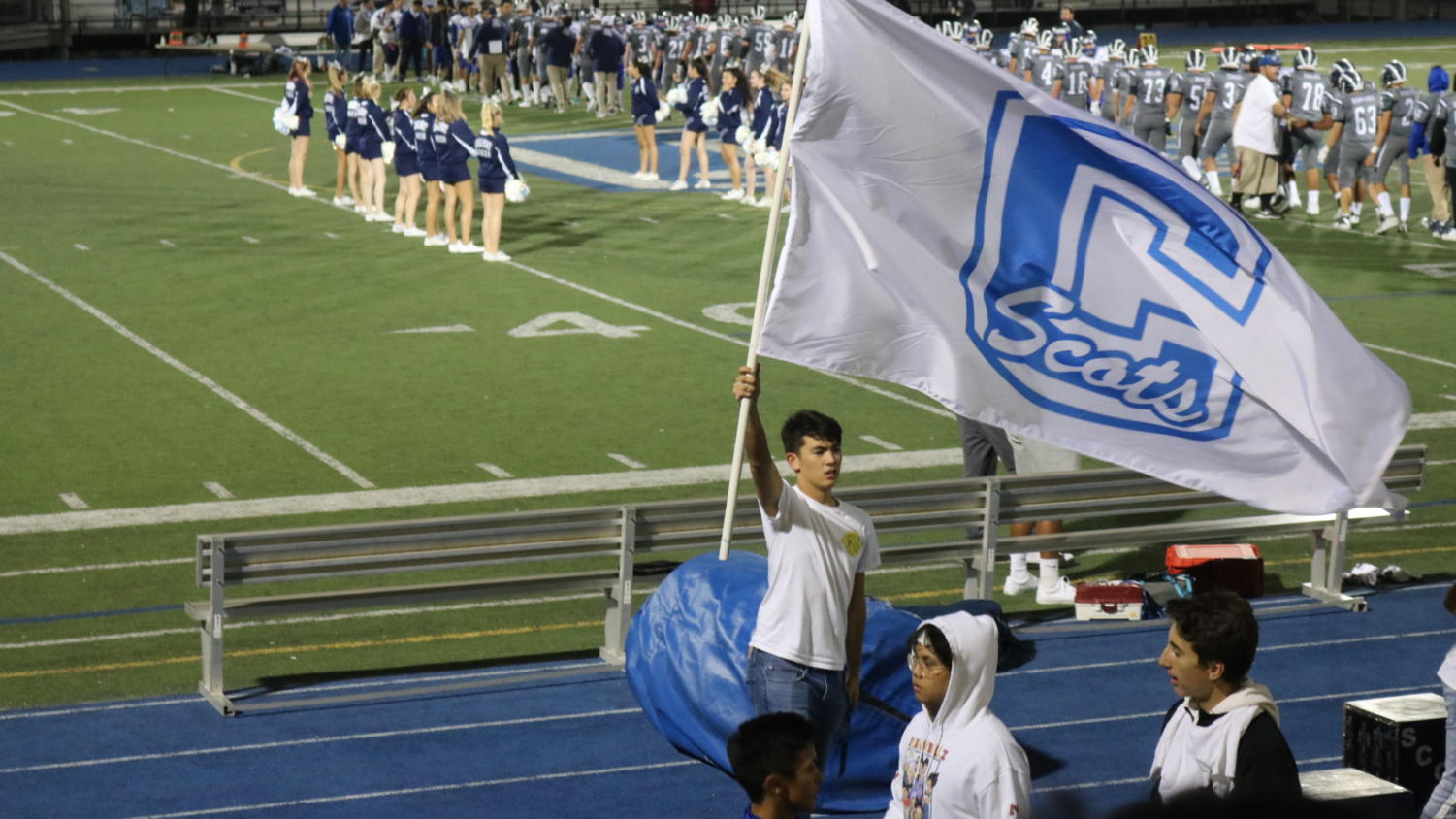ASB member Nate Rutter waves the Carlmont flag for the crowd as the cheer and football teams meet on the field.
