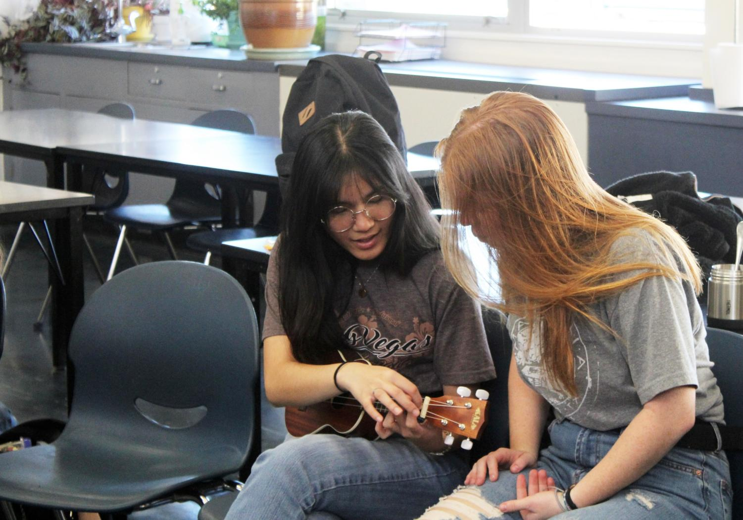 Shane Maxine Largo, a junior, and Riley Baum, a sophomore, practice playing a chord on the ukulele.