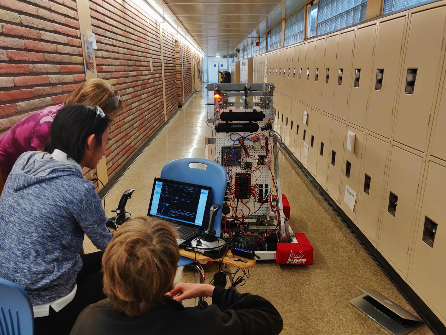Two students and a mentor work on the robot's  autonomous capabilities.