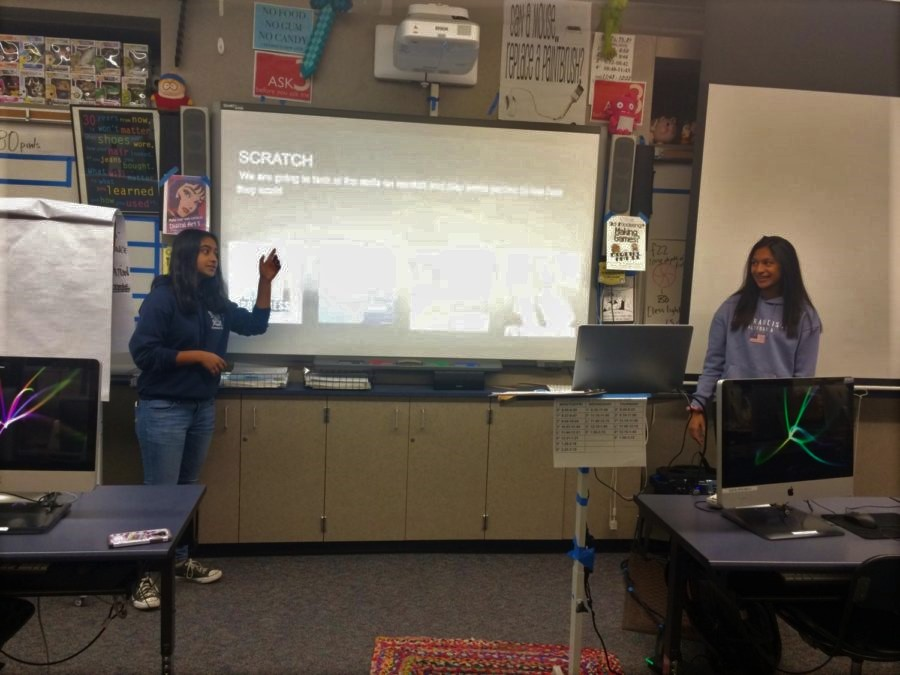 Club leaders Raina Lahiri and Amisha Nambiar give a presentation during a club meeting. Coding related memes are added to the presentation to engage club members.