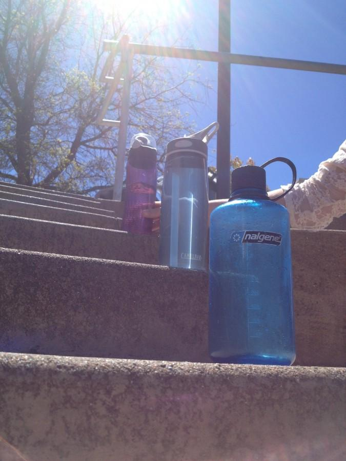 three reusable water bottles on stairs in the quad