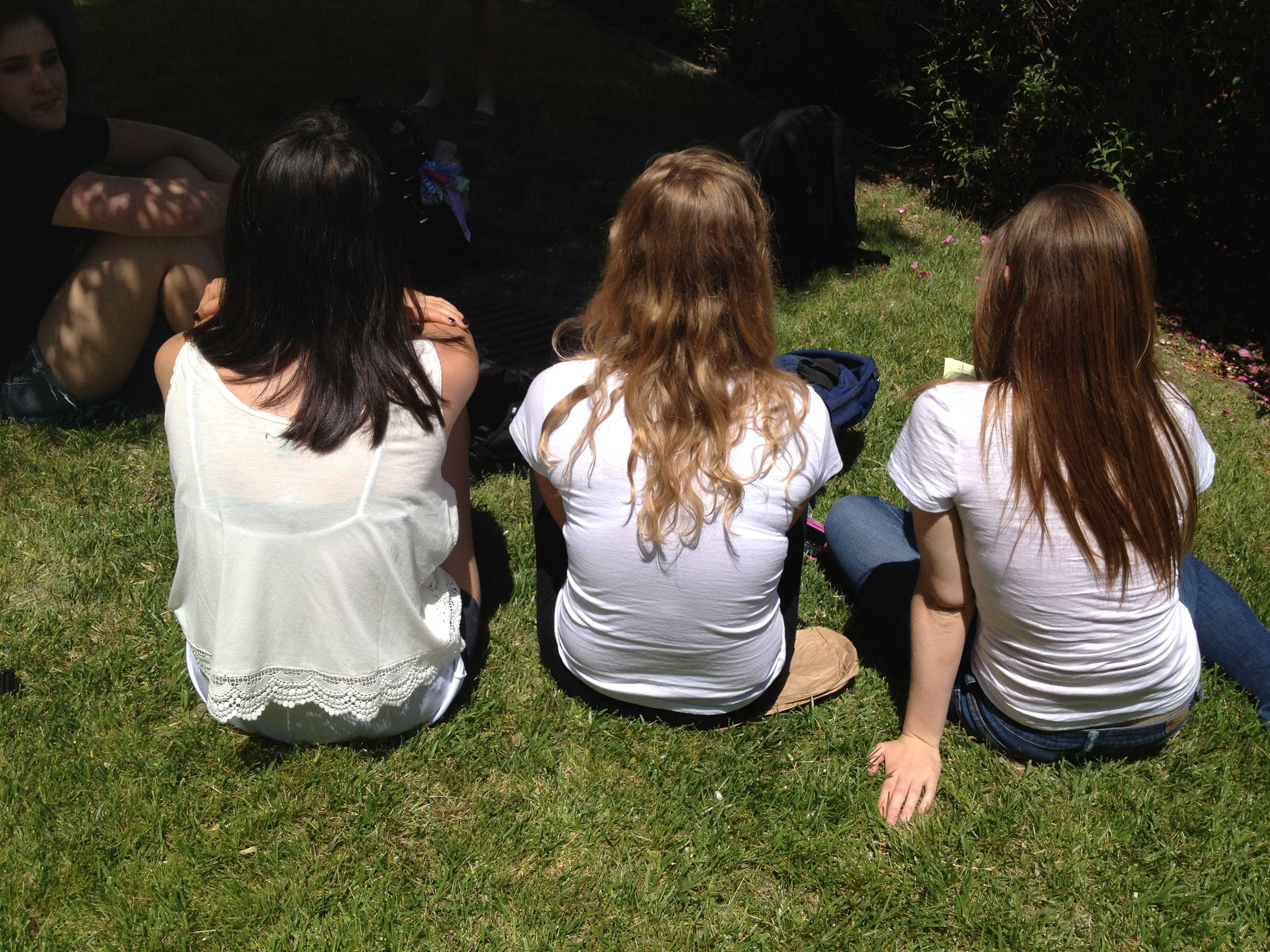Students who are wearing white enjoy eating lunch in the sun.