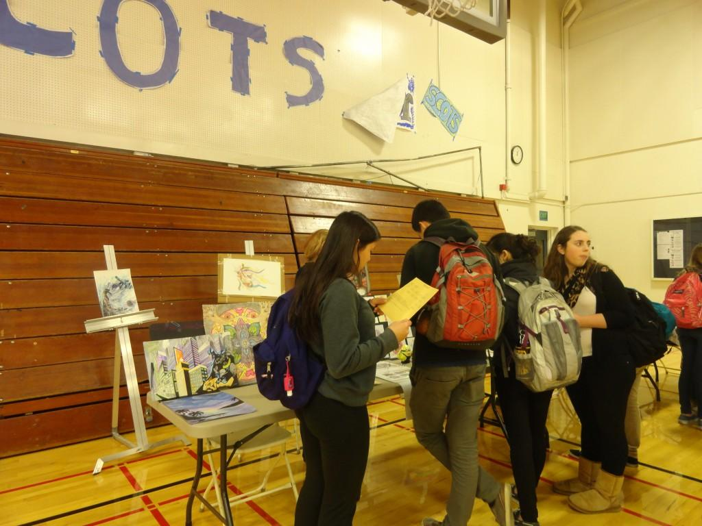 Students ask the art teachers about their class and view other student's artwork.