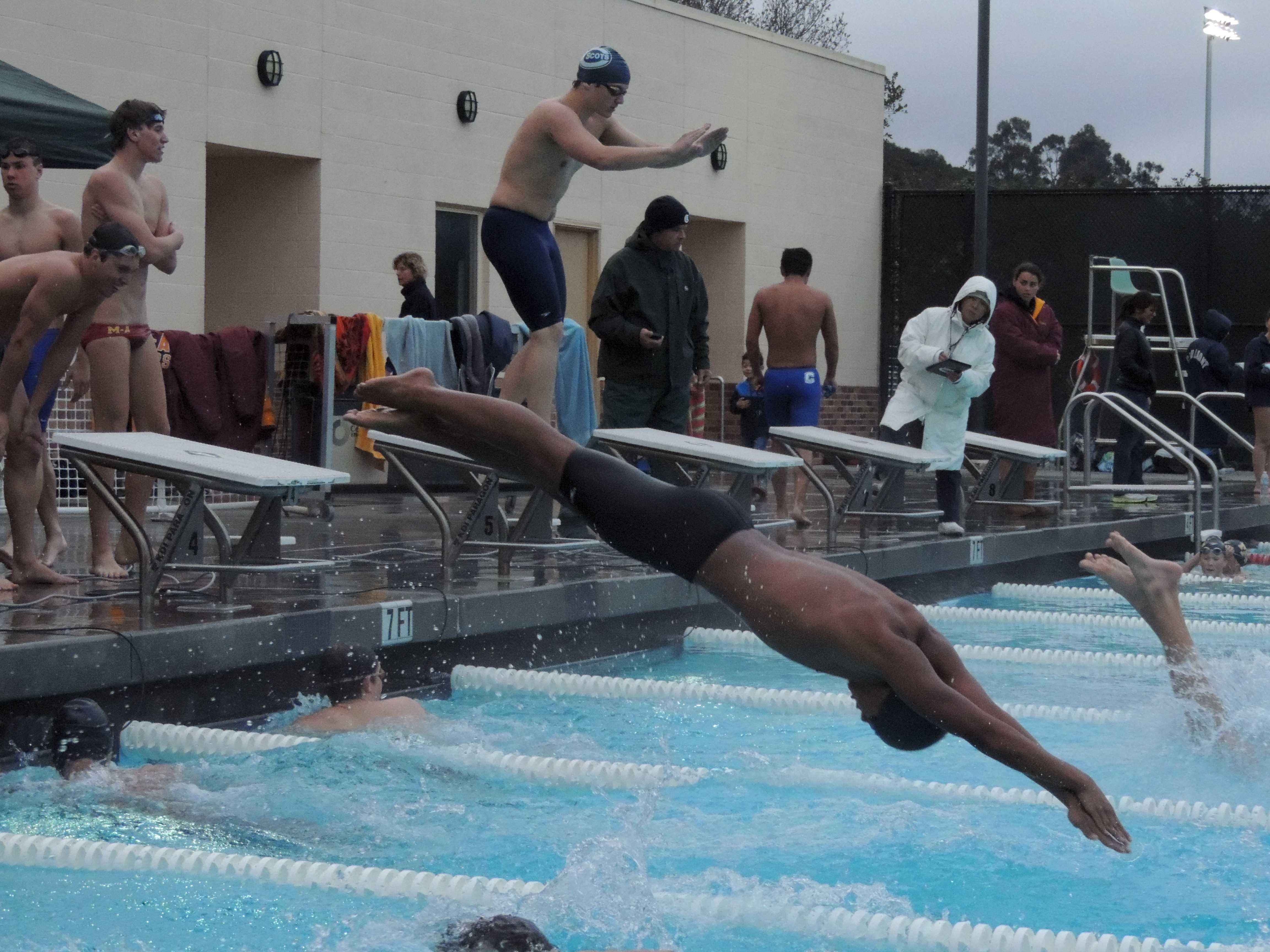 Varsity swimmer Nico Camerino dives into the pool at the beginning of the 100 freestyle relay.