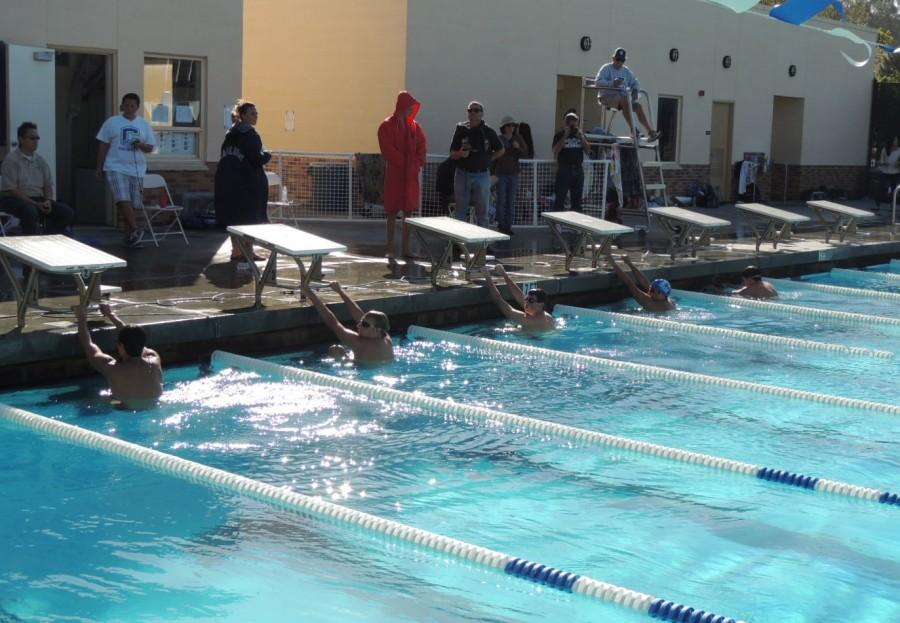 Carlmont and Burlingame swimmers prepare at the wall before a 100 meter backstroke.