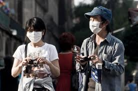 Tourists arrive at circuit wearing face-masks after a recent outbreak of the bird flu virus