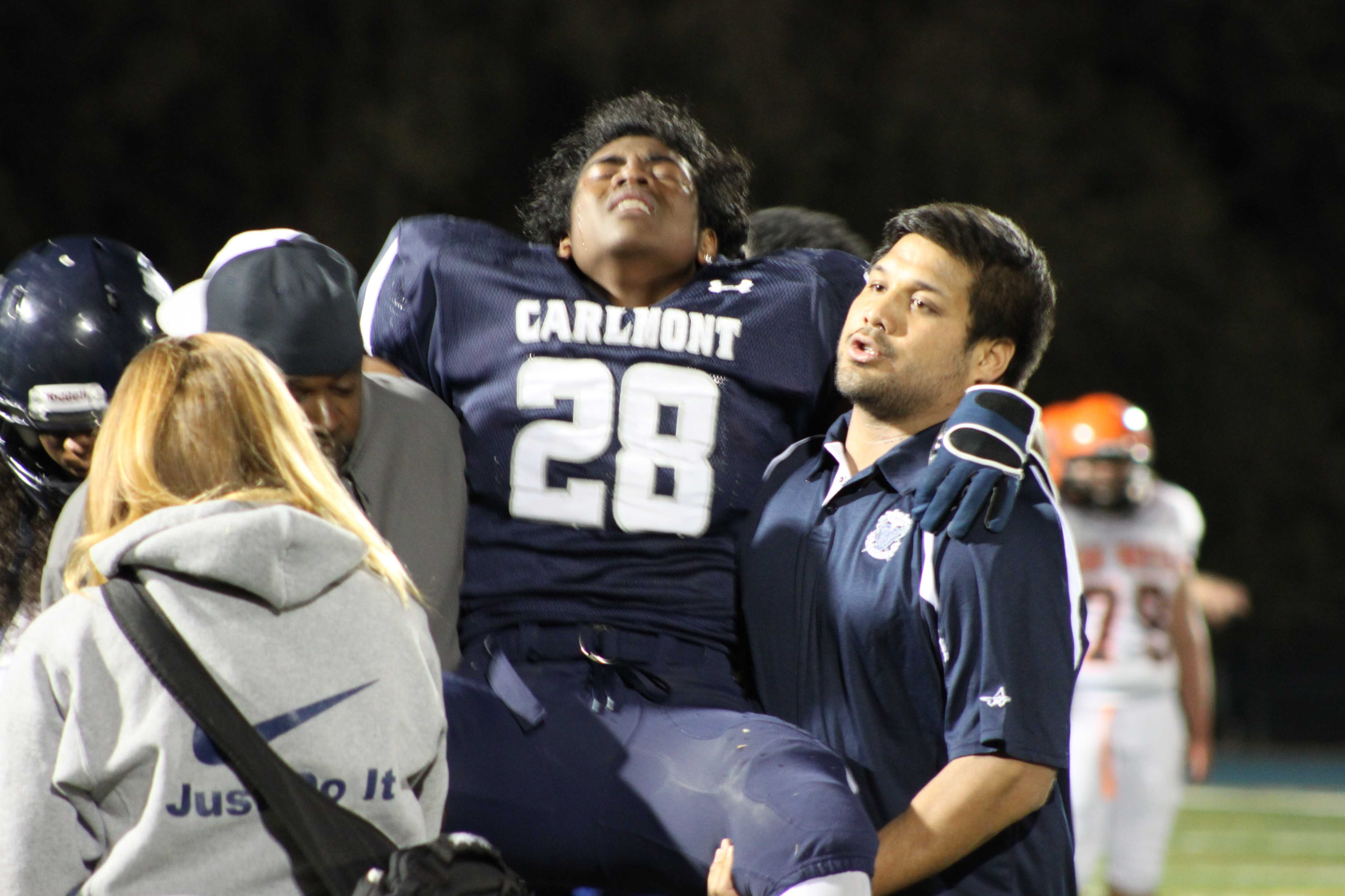 Dominic Blanks (28) getting carried off the field after being injured in the 2nd quarter.