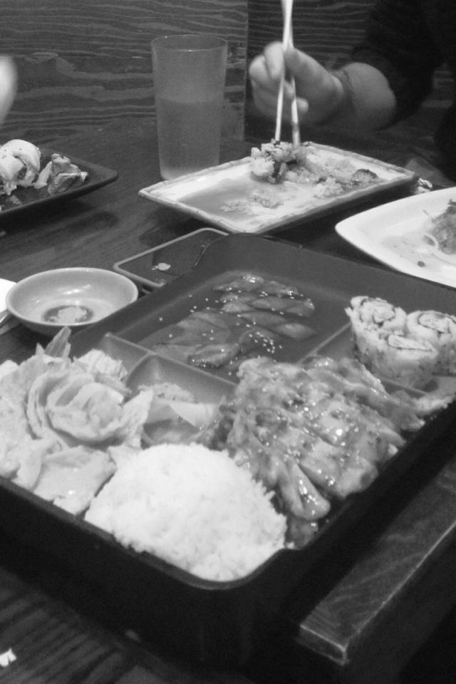 Appetizing teriyaki chicken bento box with tempura shrimp, white rice and California rolls.