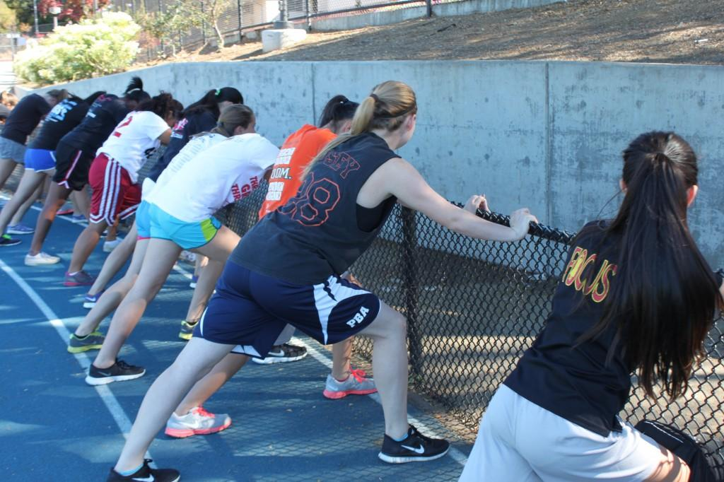 During a conditioning session for basketball, freshman Mikayla Fong (far right) and junior Erin Lucett (second right) lead the team in a wall stretch to loosen their muscles.