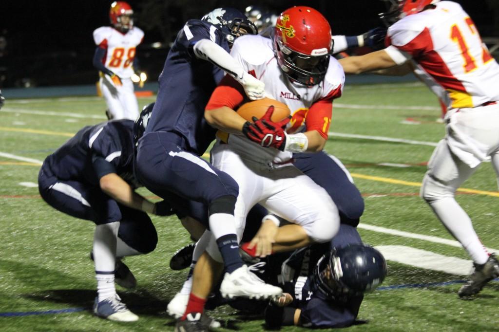 Varsity+Football+puts+up+a+defensive+battle+against+Mills