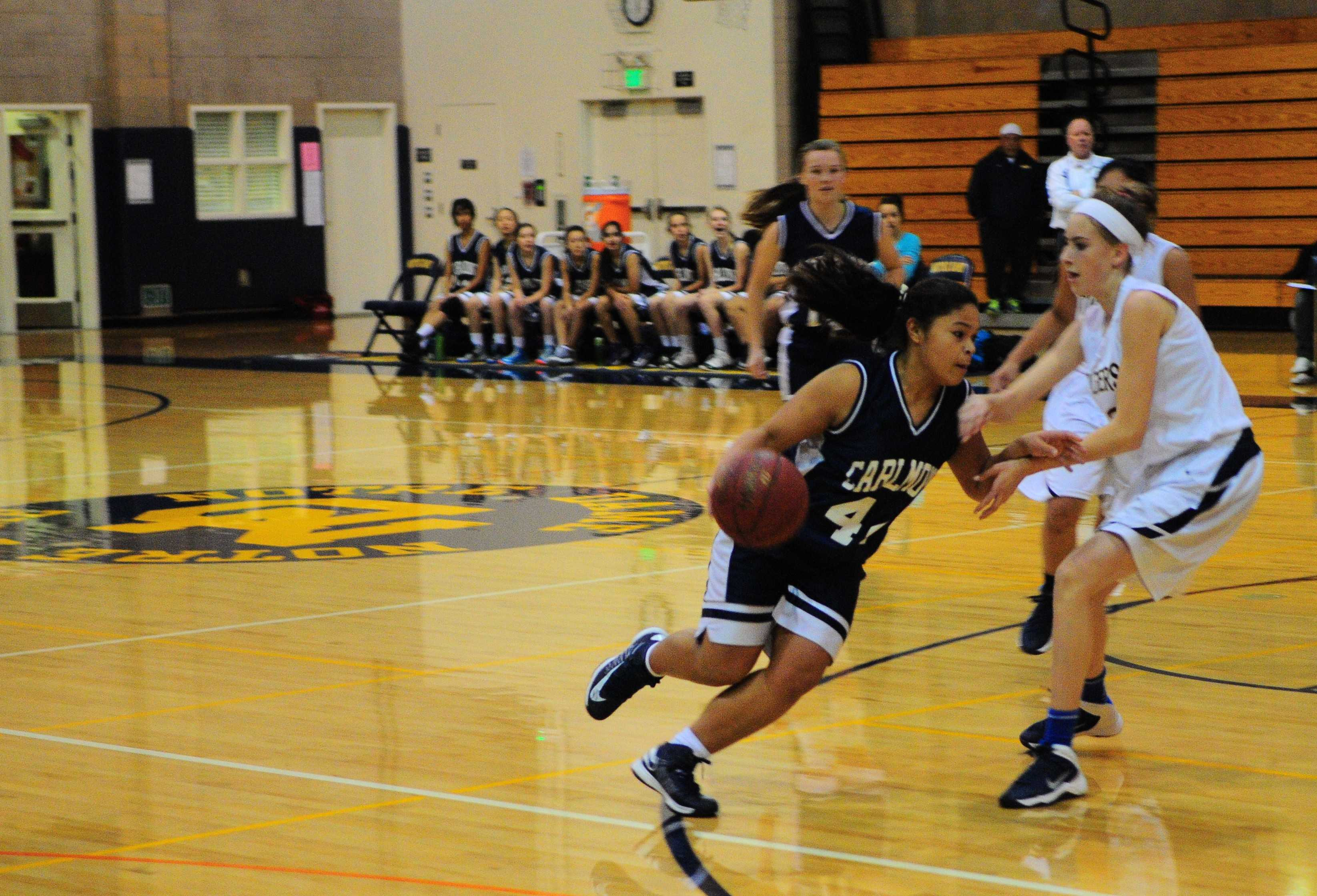 Sophomore Vianka Adamovitch dribbles around her opponent, trying to shoot a basket for Carlmont.
