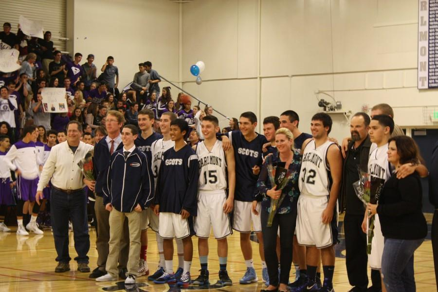 The Boys Varsity Basketball team smiles for a picture before the game.