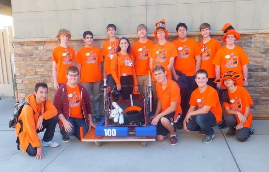 Team+100+Wildhats+displays+one+of+their+finished+robots%2C+built+by+hand.