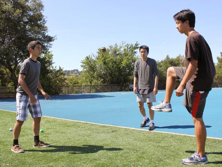 Sophomores Jack Cinque, Angelo Zhao, and Justin Tsuchiyama play hacky sack on the field after seventh period.