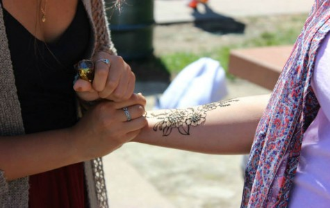 Senior Emma Lin adds the finishing touches to a student's henna tattoo at the Club Fair.