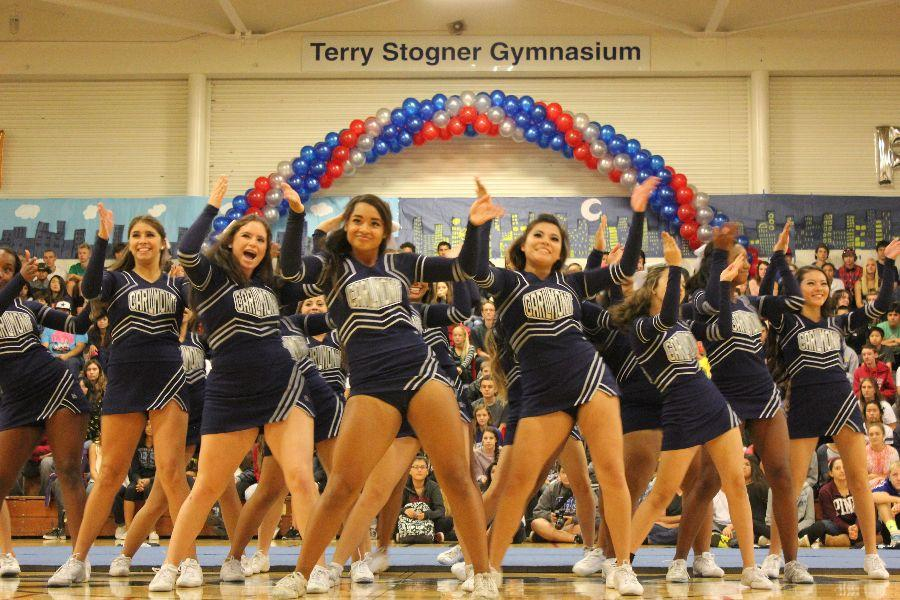 Cheer excites the crowd at the 2014 homecoming assembly. The Cheer members support each other in doing what they love.