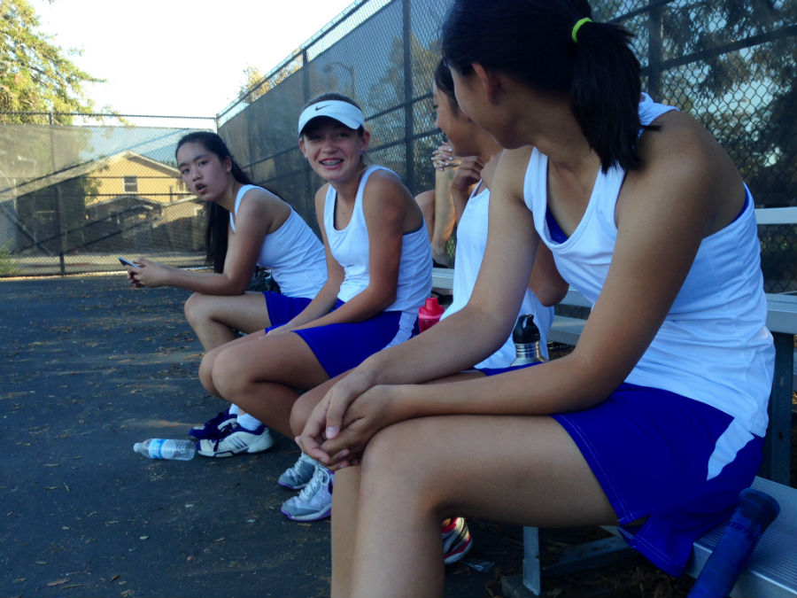 Ivy Nguyen, Juliette Rencoret and Jessica Ma converse on the sidelines of a tennis match against Sequoia High School.