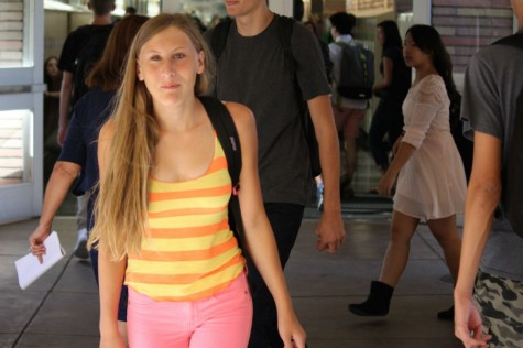 Junior Clara Romani walks the hallway during school, showing her water polo spirit with her neon outfit.