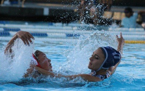 After passing the ball to her teammate, senior Sam King pushes her defender away.