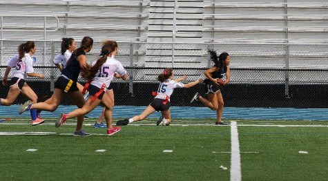 Sophomore Annabelle Lee dodges defenders as she streaks toward the end zone in the seniors versus sophomores Powderpuff game.