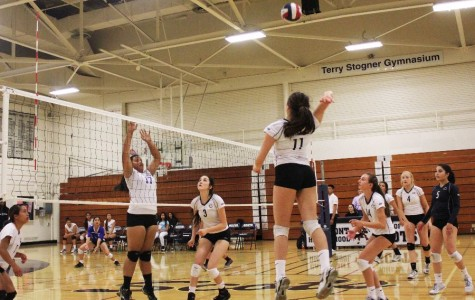 Junior Mia Hogan (11) spikes the ball in Carlmont's game against South City.