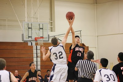 Freshman and center Matt Reiley elevates to win the jump ball for Carlmont in a 2013-2014 season game.