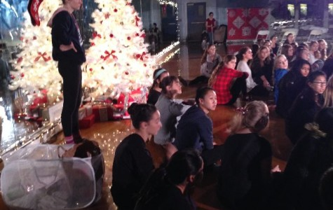 Dancers sit and listen to instructions from their teacher as they prepare for their performance.