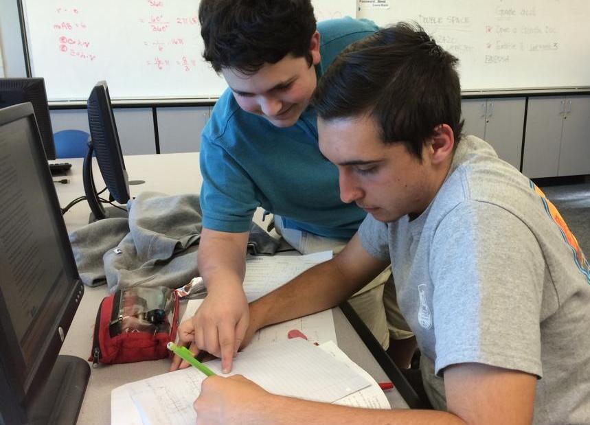Junior Aaron Yofin helps Bijan Khalili with math homework at the tutoring center.