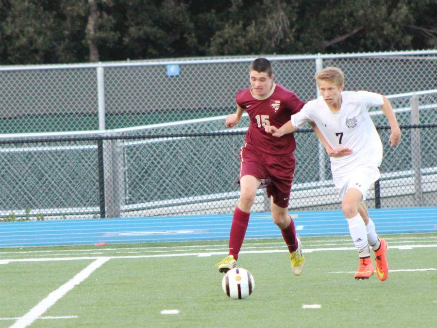 Sophomore Brett Fitzpatrick sprints beside an M-A defender.