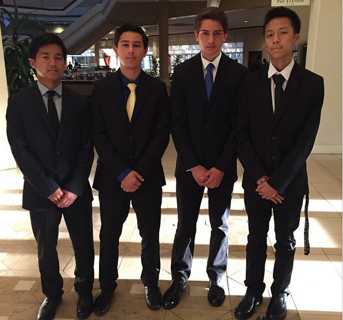 Liam Jocson, Spencer Enriquez, River Manochio, and Ethan Wong pose at the DECA LACE conference in their business attire.