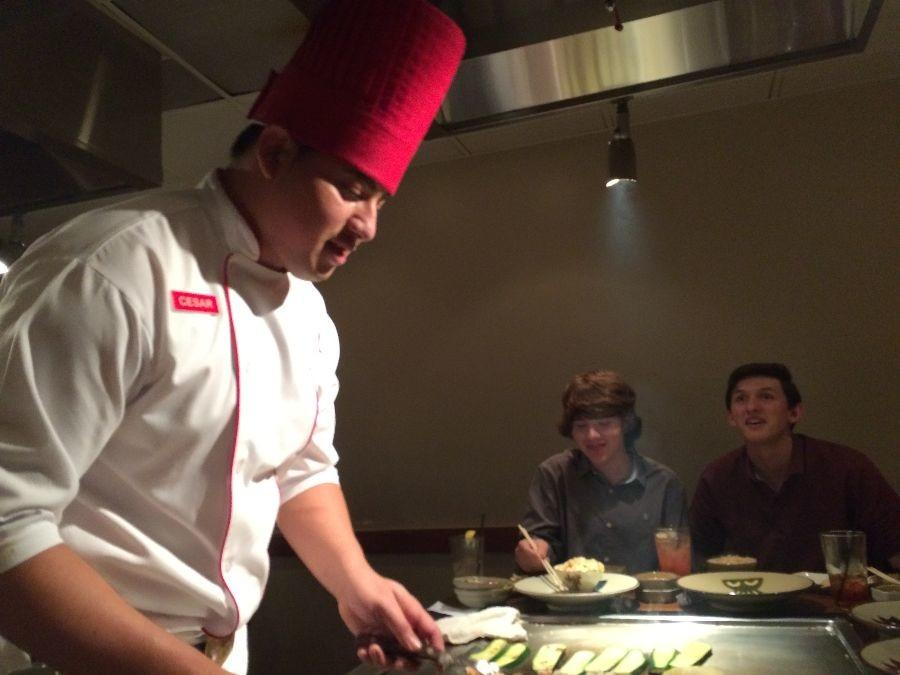 At+Benihana%2C+guests+patiently+watch+as+their+chef+cooks+their+food+on+the+grill+right+in+front+of+them.