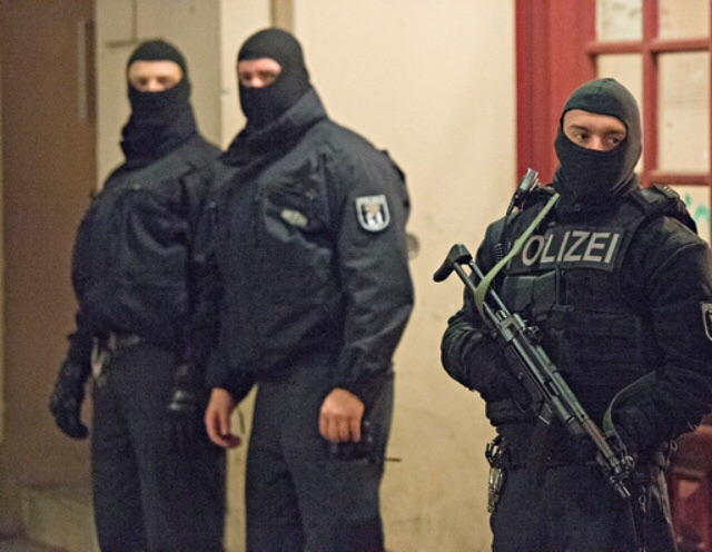Belgian police officers stand watching for threats of terrorist attacks.