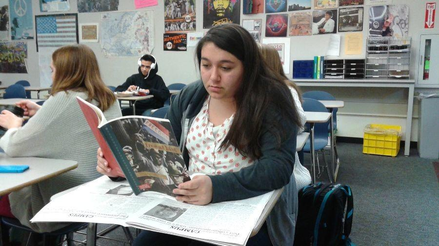 Senior+Gaby+Prado+gets+ready+for+Sojourn+to+the+Past+by+reading+a+book+on+the+Civil+Rights+Movement+.