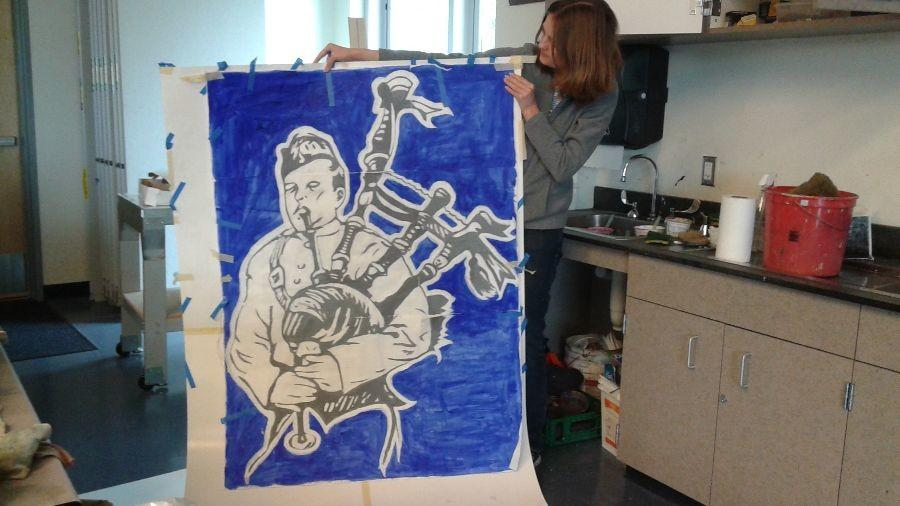 Emily Kelvin displays the stencil of Carlmont's mascot that the art club has been working  on.