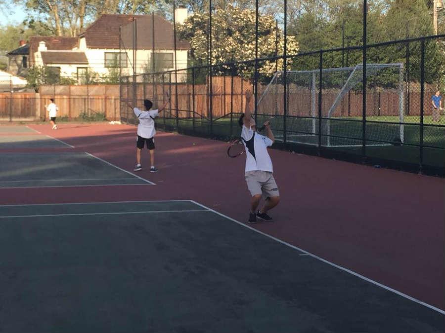 Sophmore+Victor+Li+serves+on+the+deuce+side+of+the+court.