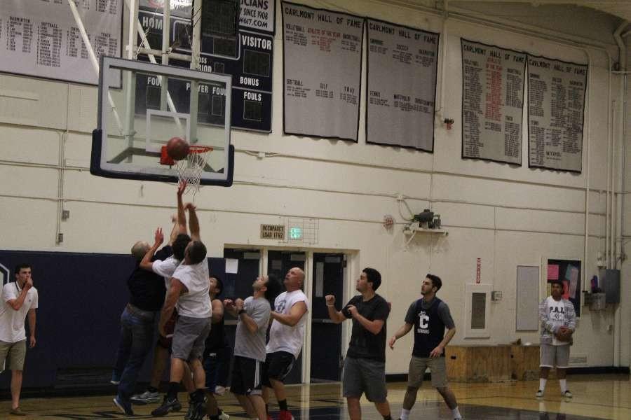 Teachers and seniors struggle for the ball.