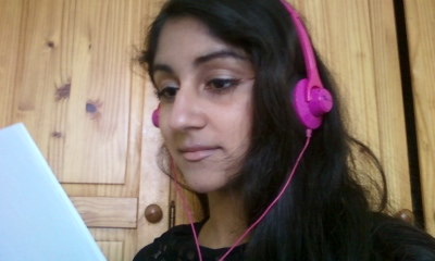 Senior Nisha Aeri reads lyrics while listening to music through her hot pink headphones.
