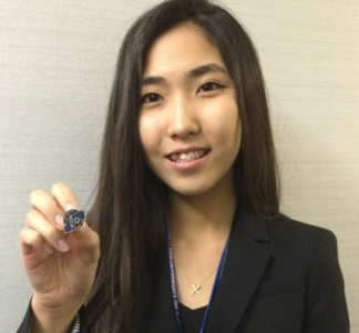 Sophomore Bo Yoon Lee shows off her top eight finalist pin after getting off stage.