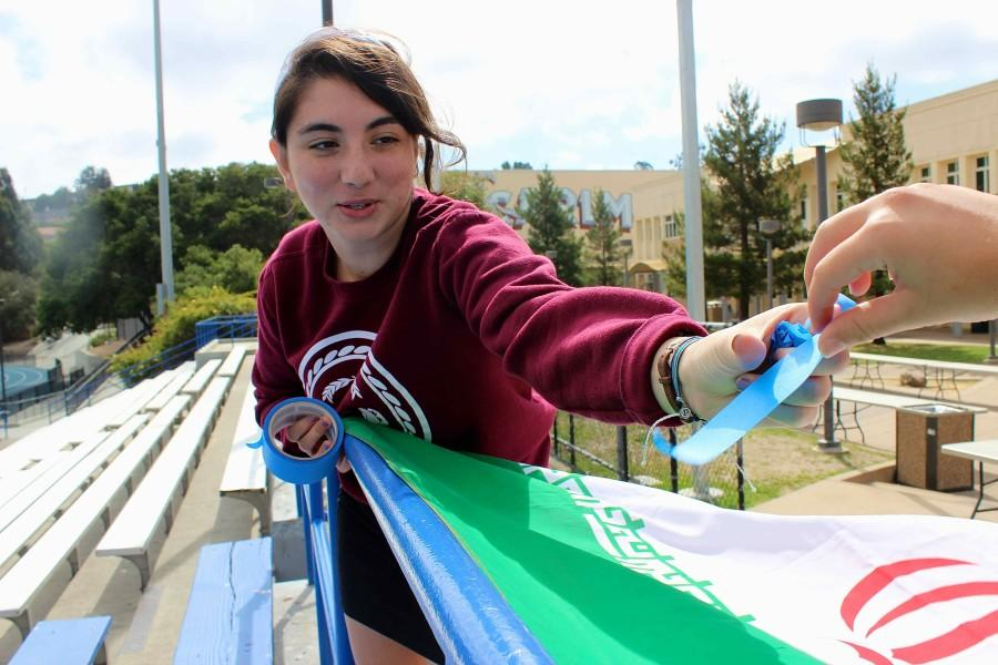 Senior Sage Shamsai hangs the Iranian flag up for Persian Club in preparation for Carlmont's 2015 club fair.