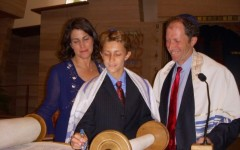 Former Carlmont student Josh Fagel stands with his parents as he reads the Torah, the central text of Judaism.