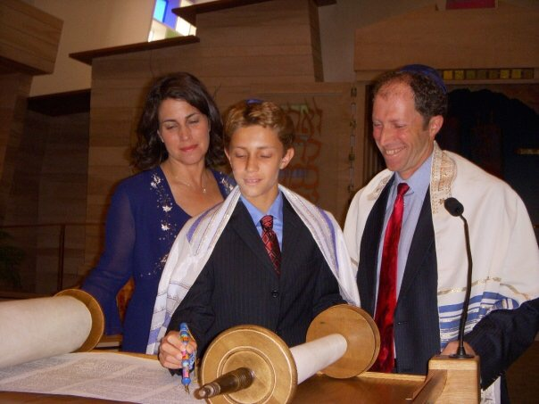 Former+Carlmont+student+Josh+Fagel+stands+with+his+parents+as+he+reads+the+Torah%2C+the+central+text+of+Judaism.